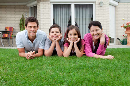 outside of house: Portrait of family of four lying on lawn in their backyard