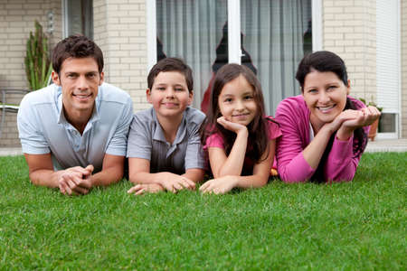 backyard woman: Portrait of happy young family lying on grass outside their house Stock Photo