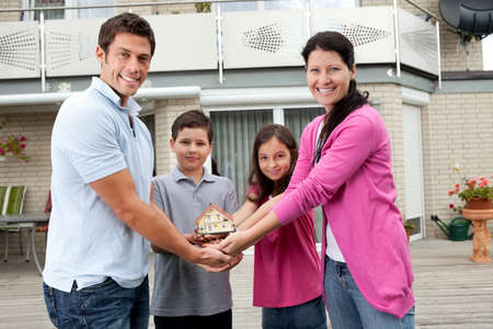miniature people: Portrait of young family of four holding a model of house - Outdoors