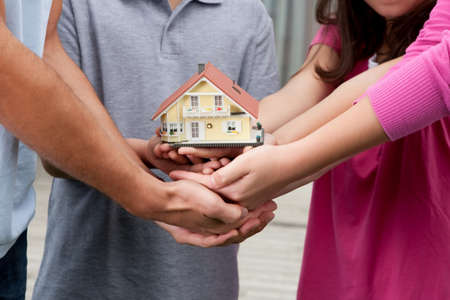 hands holding house: Closeup of human hands holding a miniature model of house