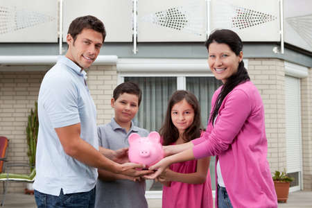 Portrait of happy family holding piggy bank outside their house photo