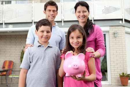 save money: Portrait of cute little girl holding a piggy bank with her family Stock Photo