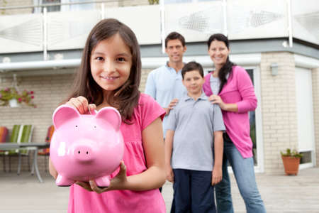 Beautiful little girl inserting coin in a piggy bank with her family in background photo