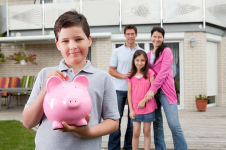 finance girl: Adorable little boy inserting coin in a piggy bank with her family in background