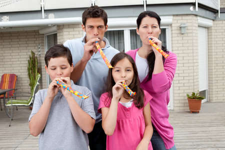 Portrait of happy family blowing whistle and having fun in backyard photo