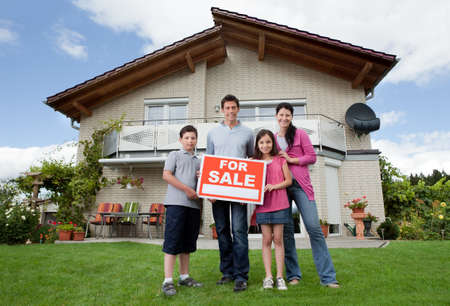 selling house: Portrait of young family selling their home holding for sale sign