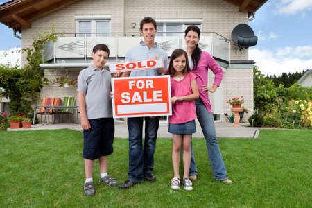 real estate: Portrait of happy young family in front of new home with sold real estate sign