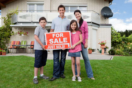 selling house: Young happy family holding sold sign outside their new house Stock Photo