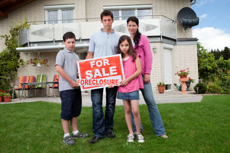 Portrait of young family holding a foreclosure sign outside their house photo