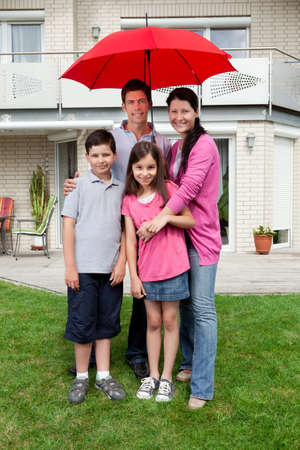 Joven familia feliz de pie bajo un mismo paraguas fuera de su casa Foto de archivo