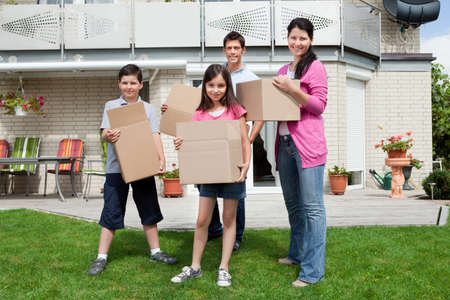 Happy family with cardboard boxes moving in their new home photo