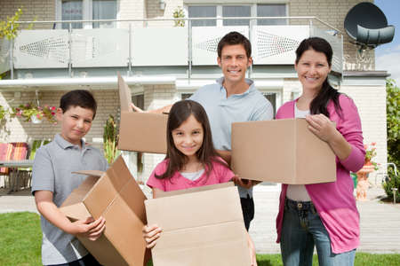 family moving house: Happy young family moving into new home carrying boxes
