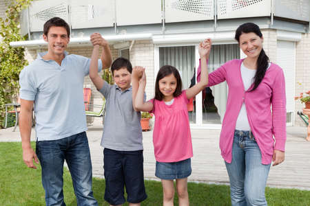 children holding hands: Happy family standing together holding hands outside their home