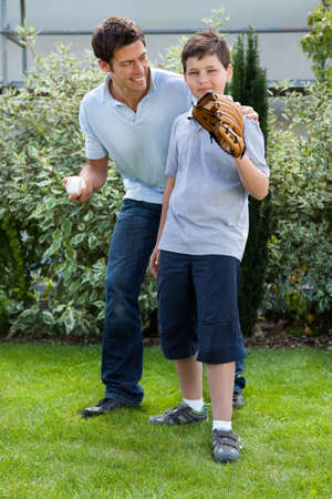 Loving little boy playing baseball with his father in their backyard photo
