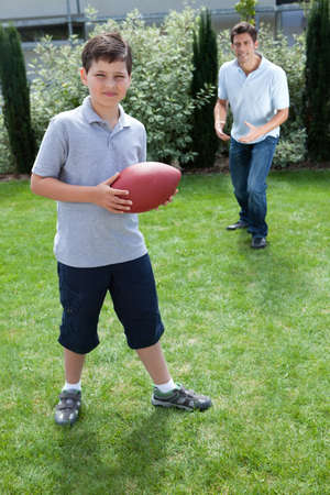 Cute little boy playing american football with his father photo