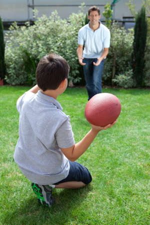 Little kid throwing football to his father in backyard photo