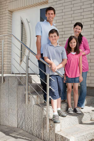 Portrait of happy young family standing at doorstep photo