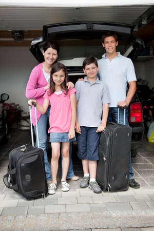 preteens girl: Happy family going on holiday standing by their car boot with their luggage