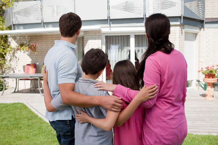 buy house: Buying new home - Family standing in front of their new house