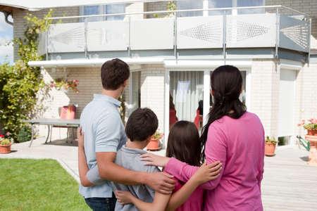 Vista posteriore della giovane famiglia in piedi di fronte alla loro casa dei sogni