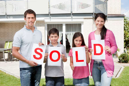 selling house: Portrait of young family holding a sold sign in front of their home
