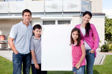 Portrait of happy young family standing outside with a blank sign board photo