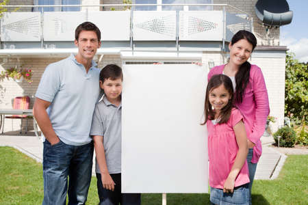 Portrait of small family standing outside with a empty sign board photo
