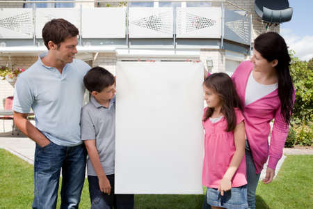 Young family looking at a empty sign board outside their house photo