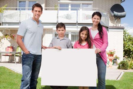 ni�os sosteniendo un cartel: Retrato de familia joven que sostiene un tablero blanco, negro, fuera de su casa