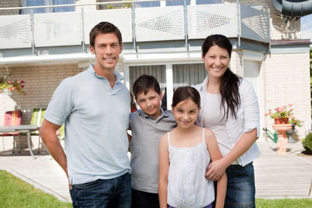 Portrait of caucasian family standing together in front of their new house photo