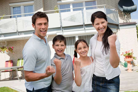 Portrait of excited family celebrating success in front of their home photo