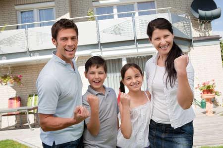 ganar: Retrato de familia emocionados celebrando el �xito en el frente de su casa