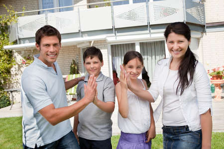 eachother: Portrait of happy young family giving high five to eachother Stock Photo