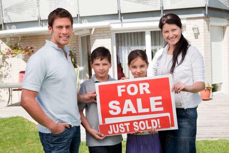 vendiendo: Retrato de joven familia feliz con una muestra de la venta fuera de su casa