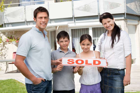 sold small: Smiling young family with a sold sign standing outside their new house