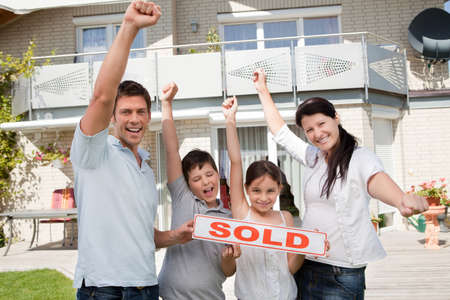 sold small: Portrait of happy young family celebrating buying their new house Stock Photo