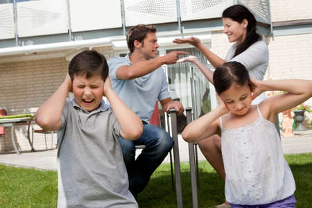 Little children covers their ears as their parents argue loudly behind photo