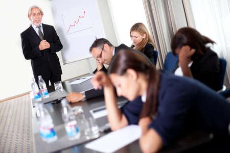 boring: Businessman discussing sales targets at a meeting with his inattentive and sleepy team