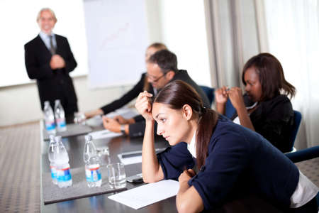 boring: Young businessman discussing work with his colleagues at a meeting room Stock Photo