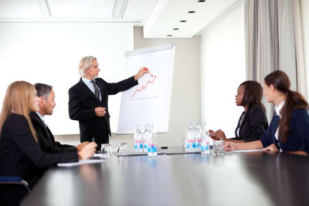presentation board: Senior male speaker giving presentation at a business meeting Stock Photo