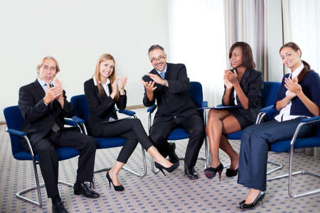 Portrait of a team of happy successful businesspeople sitting together smiling and celebrating at the office photo