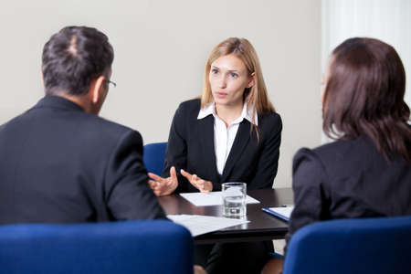 law: Pretty young woman explaning about her profile to business managers at a job interview