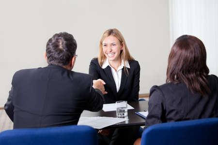 entrevista de trabajo: Confianza feliz joven candidato mujeres dar la mano durante una entrevista de trabajo en la oficina con los administradores