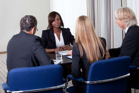 Group of managers interviewing pretty young female candidate for job at the office photo