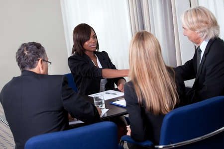 Mature group of business managers conducting job interview shaking hands with applicant at a table in meeting room photo