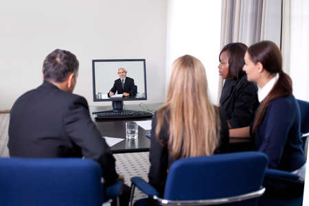 CONFERENCE TABLE: Group of successful young businesspeople at a video conference in the office Stock Photo