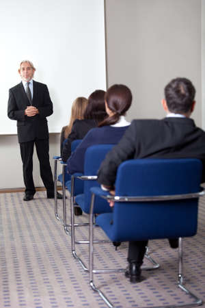 job training: Mature business man giving presentation to his colleagues at a meeting room