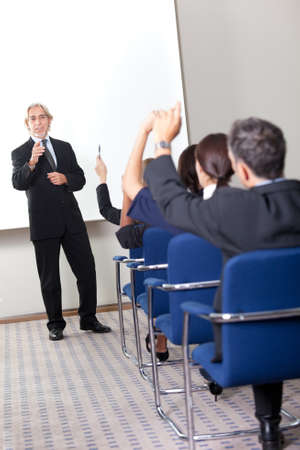 raise hand: Portrait of a confident senior manager giving presentation to his colleagues at office