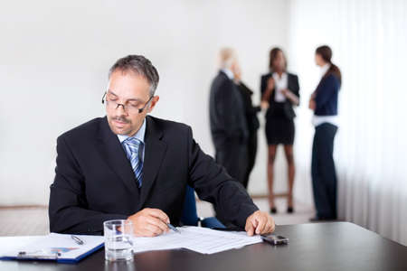 Confident businessman reading and writing at his office Stock Photo - 11080251