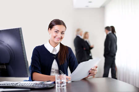 office use: Closeup portrait of happy young business woman holding important office documents and smiling at the camera with colleagues